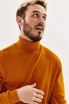 L'homme dans un chandail à côté de vêtements pour hommes de coiffure à la mode en gros plan