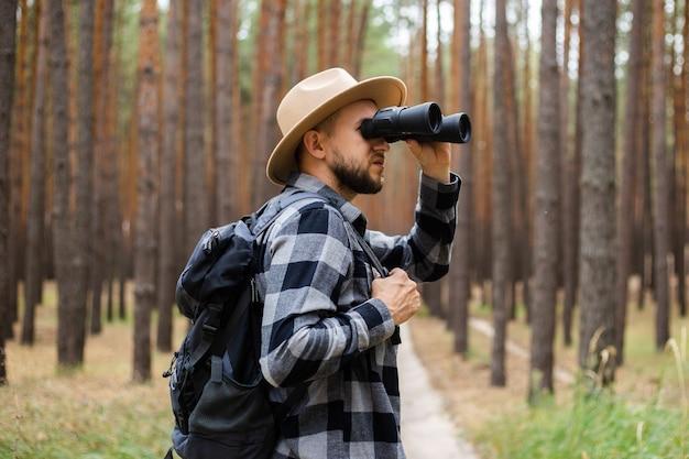 L'homme dans un chapeau et une chemise à carreaux tient des jumelles et se promène dans la forêt.