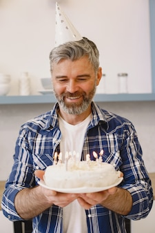 L'homme dans un chapeau de fête garde un gâteau avec des bougies. l'homme porte une chemise.