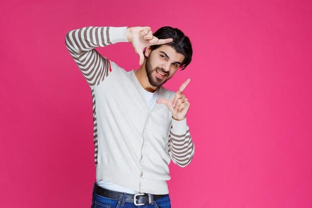 Homme dans une chemise blanche faisant le symbole du cadre photo.