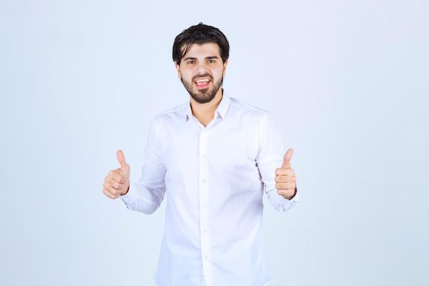 Homme dans une chemise blanche montrant le signe de la main de plaisir