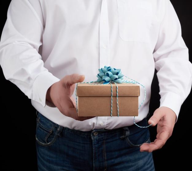 L'homme dans une chemise blanche tient dans sa main une boîte cadeau brune fermée sur un fond sombre