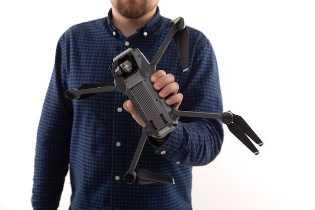 Un homme dans une chemise bleue tenant un quadcopter sur un fond blanc