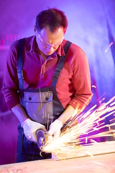 Homme, dans, combinaison, lunettes protectrices, et, gants, broyage, métal, à, écoulement, étincelles, dans, garage