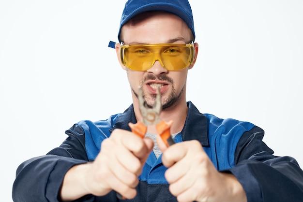 L'homme dans la construction des pinces uniformes répare les professionnels de la construction