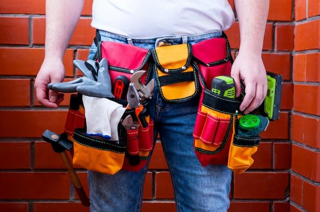 Un homme dans le contexte d'un mur de briques rouges avec un sac plein d'outils.