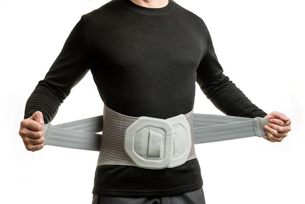 Homme dans un corset orthopédique isolé sur mur blanc