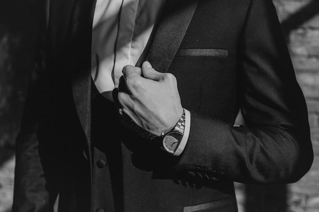 L'homme dans un costume noir élégant avec une montre sur son poignet redresse son costume