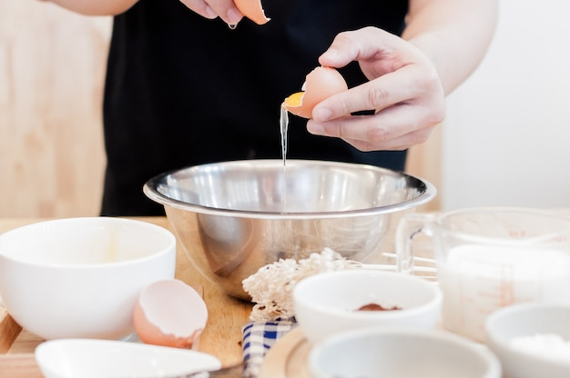 Homme dans la cuisine faisant cuire une pâte. les mains cassent un œuf dans un bol, les mains versent l'œuf mordu, le concept de cuisson