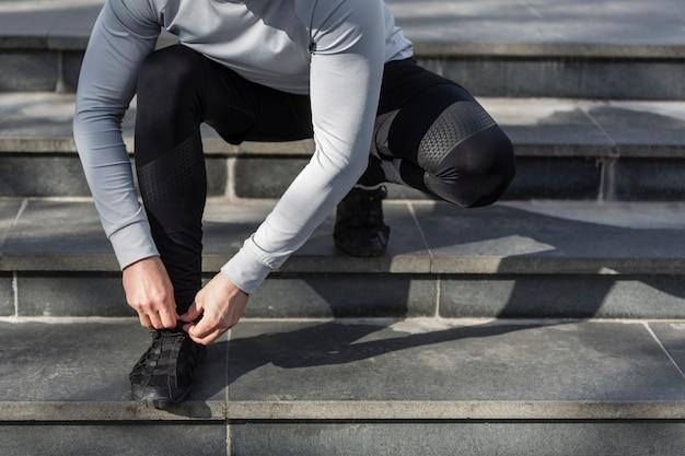 Homme dans les escaliers attachant ses lacets