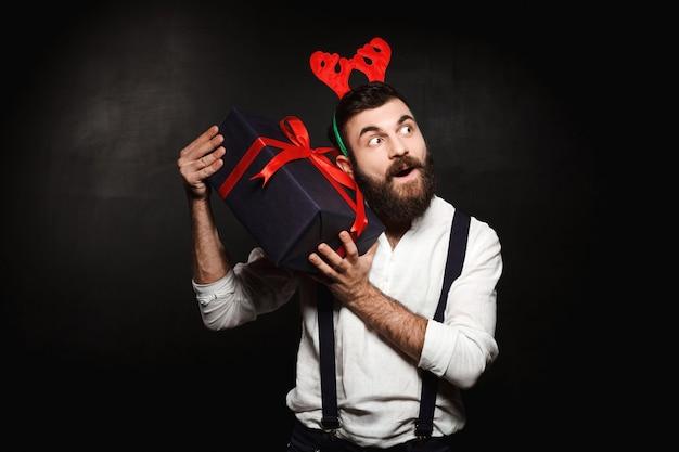 Homme dans de fausses cornes de cerf tenant une boîte-cadeau de noël sur fond noir.
