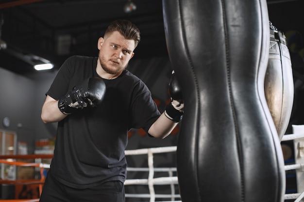 Homme dans des gants. boxer dans un vêtement de sport. guy avec une barbe.