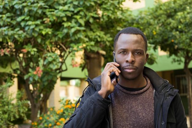 Homme dans le jardin fait un appel téléphonique