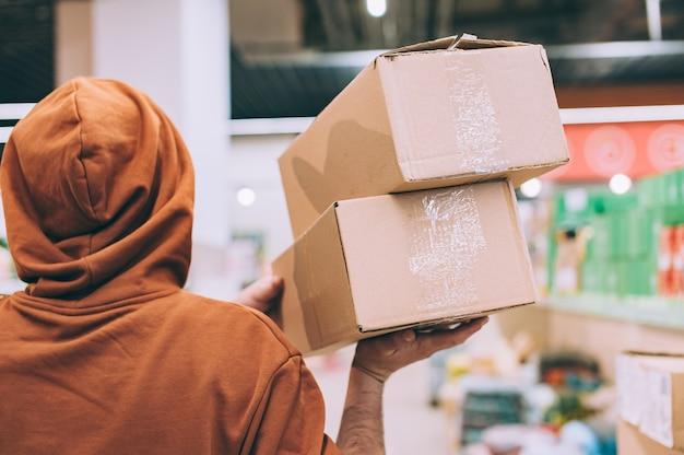 Un homme dans un magasin tient une boîte brune dans ses mains.