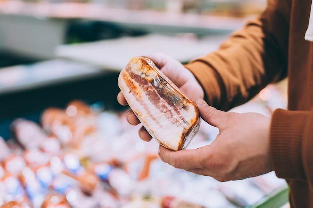 Un homme dans un magasin tient du bacon fumé dans ses mains.