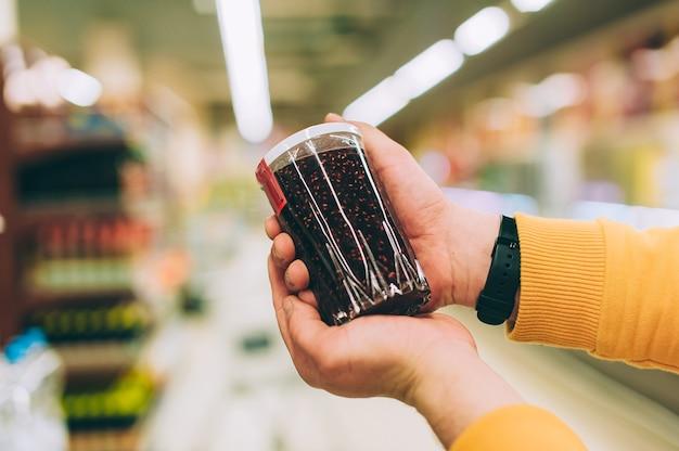Un homme dans un magasin tient un pot de confiture à la main, sur fond de rack.