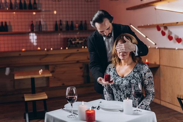 Un homme dans une main tient une boîte avec une alliance et la seconde ferme les yeux de la femme