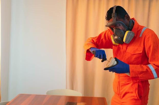 L'homme dans le masque à gaz répare un tuyau à la maison