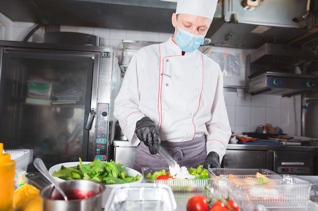 Homme dans un masque médical debout dans une cuisine