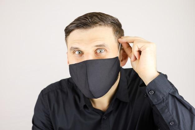 Un homme dans un masque médical noir regarde la caméra sur un fond blanc