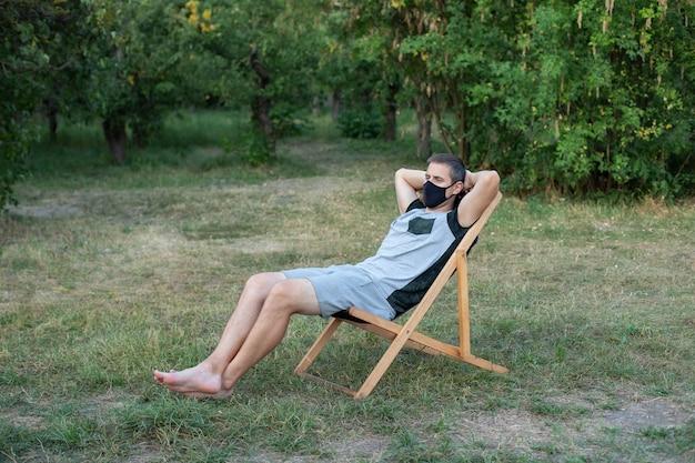 Homme dans un masque médical protecteur sur son visage bronzer sur la pelouse personne se détendre sur un transat dans le jardin