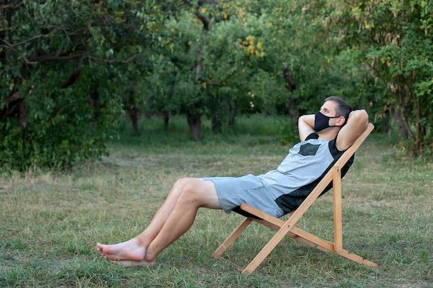 Homme dans un masque médical de protection reste sur un transat de salon personne se détendre sur une chaise longue dans le jardin