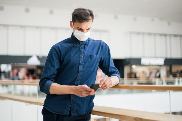 Homme dans un masque de protection avec un smartphone debout dans la rue