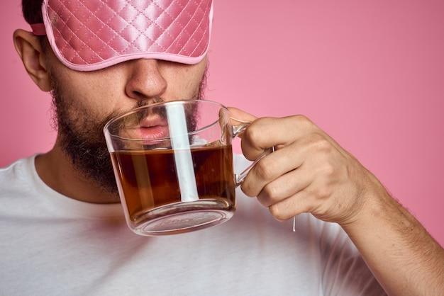 Un homme dans un masque de sommeil rose avec une tasse de thé dans ses mains