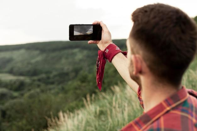Homme dans la nature prenant selfie