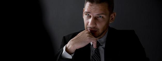 Homme dans l'ombre avec visage sérieux regardant l'interlocuteur