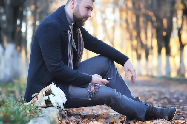 Homme dans le parc d'automne extérieur avec date de fleur de bouquet en attente