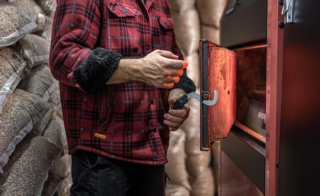 Un homme dans une pièce avec une chaudière à combustible solide, travaillant au biocarburant, chauffage économique.
