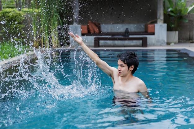 Homme dans la piscine et jouant des éclaboussures d'eau