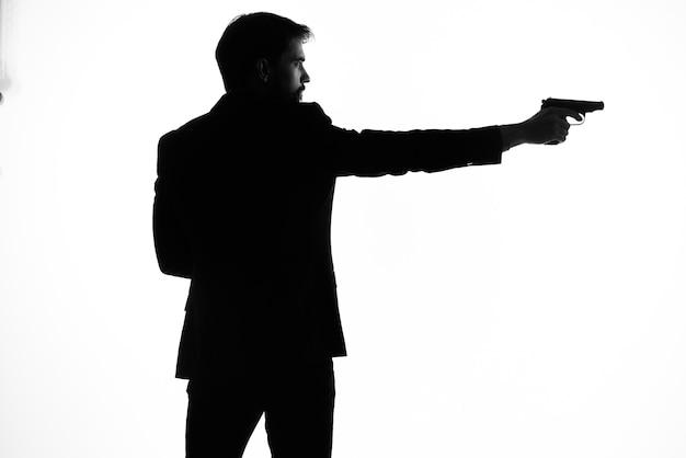 L'homme dans un pistolet de costume dans les mains du studio de pose de silhouette d'émotions