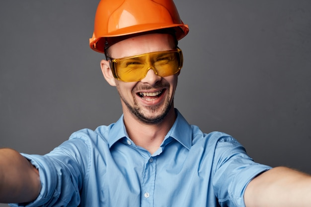 Homme dans le professionnel des émotions de constructeur de casque orange