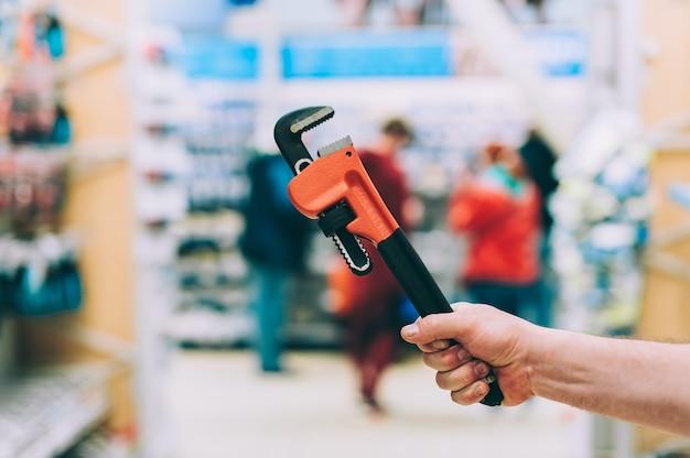 Un homme dans une quincaillerie tient une clé à molette.