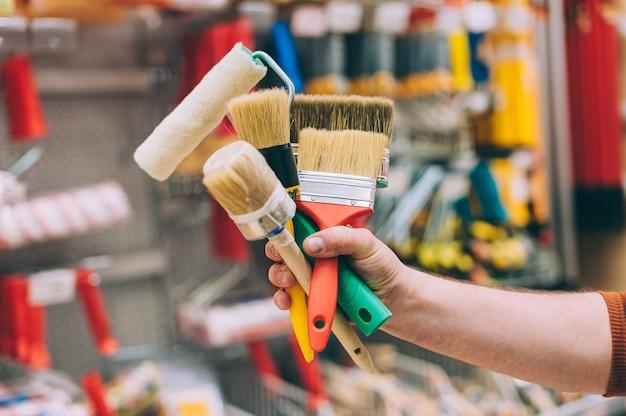 Un homme dans une quincaillerie tient un ensemble de pinceaux et de rouleaux pour la peinture et la décoration.