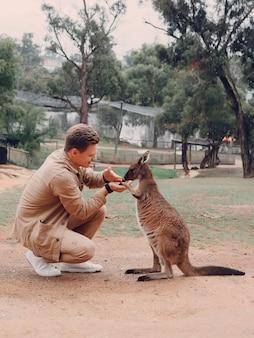 L'homme dans la réserve joue avec un kangourou