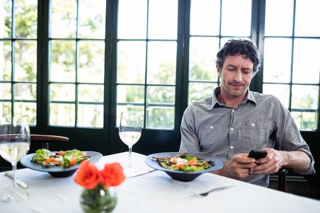 Homme dans un restaurant à l'aide d'un téléphone portable