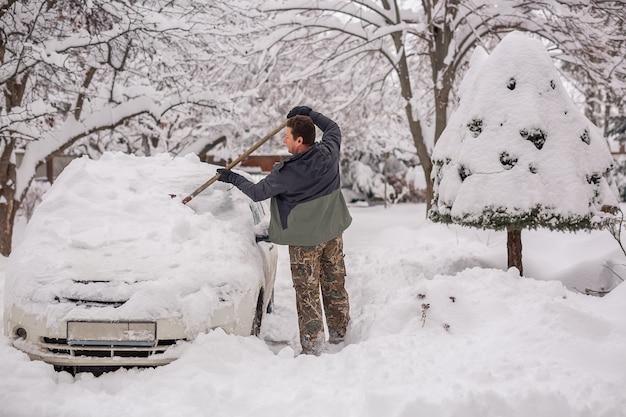 L'homme dans la rue un jour d'hiver efface la voiture de la neige