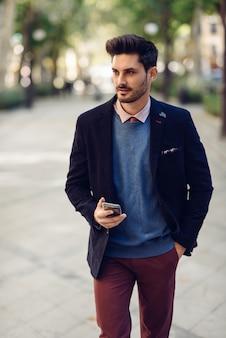 Homme dans la rue en vetu avec smartphone dans sa main.