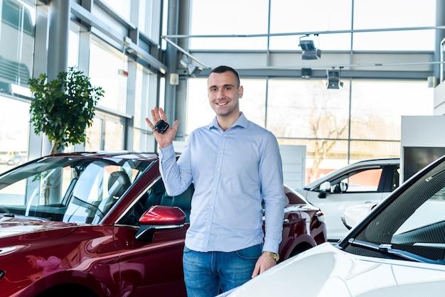 Homme dans la salle d'exposition tenant les clés d'une nouvelle voiture