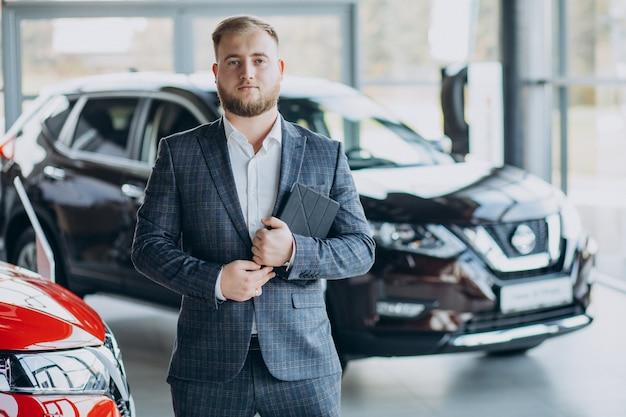 Homme dans la salle d'exposition de voiture en choisissant une voiture