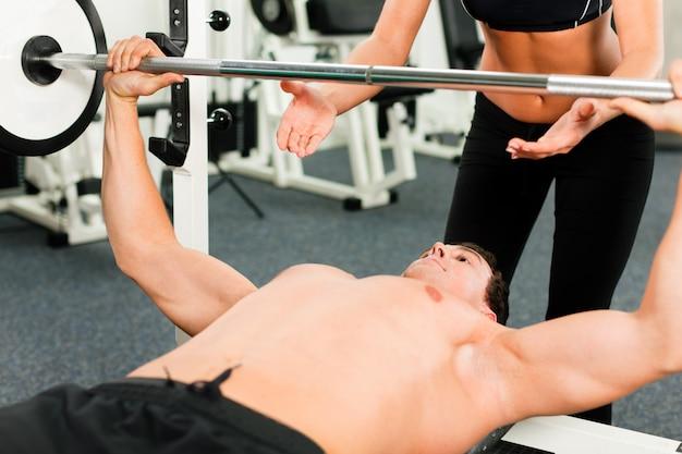 Homme dans la salle de gym avec entraîneur personnel exerçant une gymnastique de puissance avec une barre