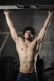 Homme dans la salle de sport faisant pull-up. bodybuilder en salle de sport
