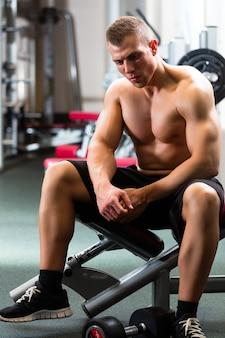 Homme dans une salle de sport ou de fitness sur banc de musculation