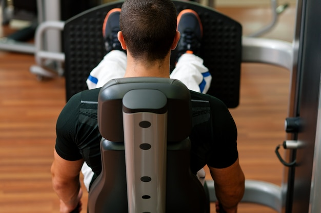 Homme dans une salle de sport sur machine à exercer