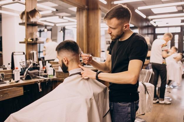 Homme dans un salon de coiffure pour coiffeur et coupe de barbe