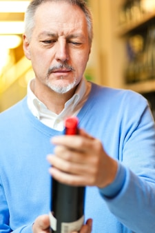 Homme dans un supermarché en choisissant une bouteille de vin