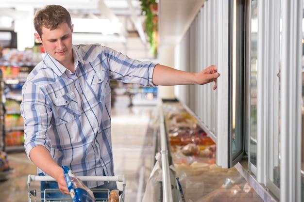 Homme dans un supermarché debout devant le congélateur